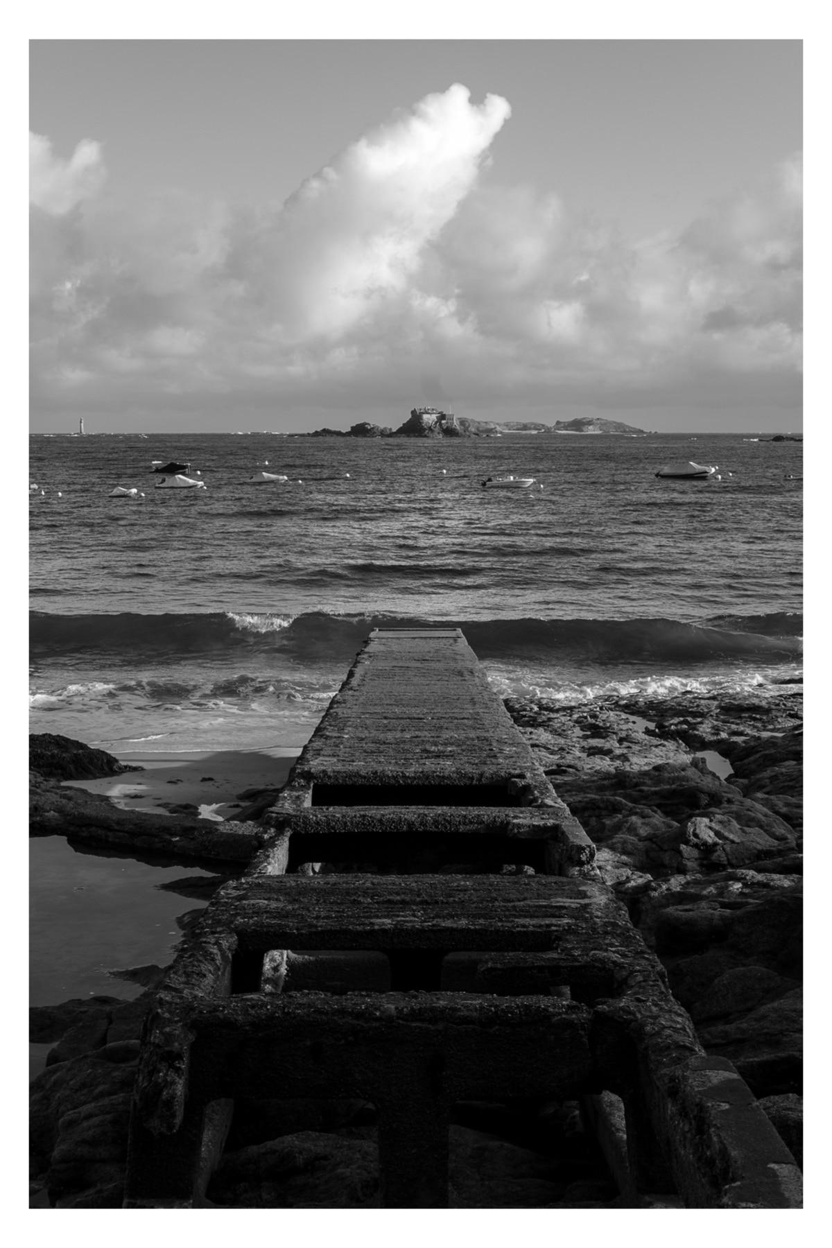 Monochrome photo of a cement pier leading into the ocean falling short of Fort de Harbour along the Chemin de Ronde de la Malouine in Dinard, France