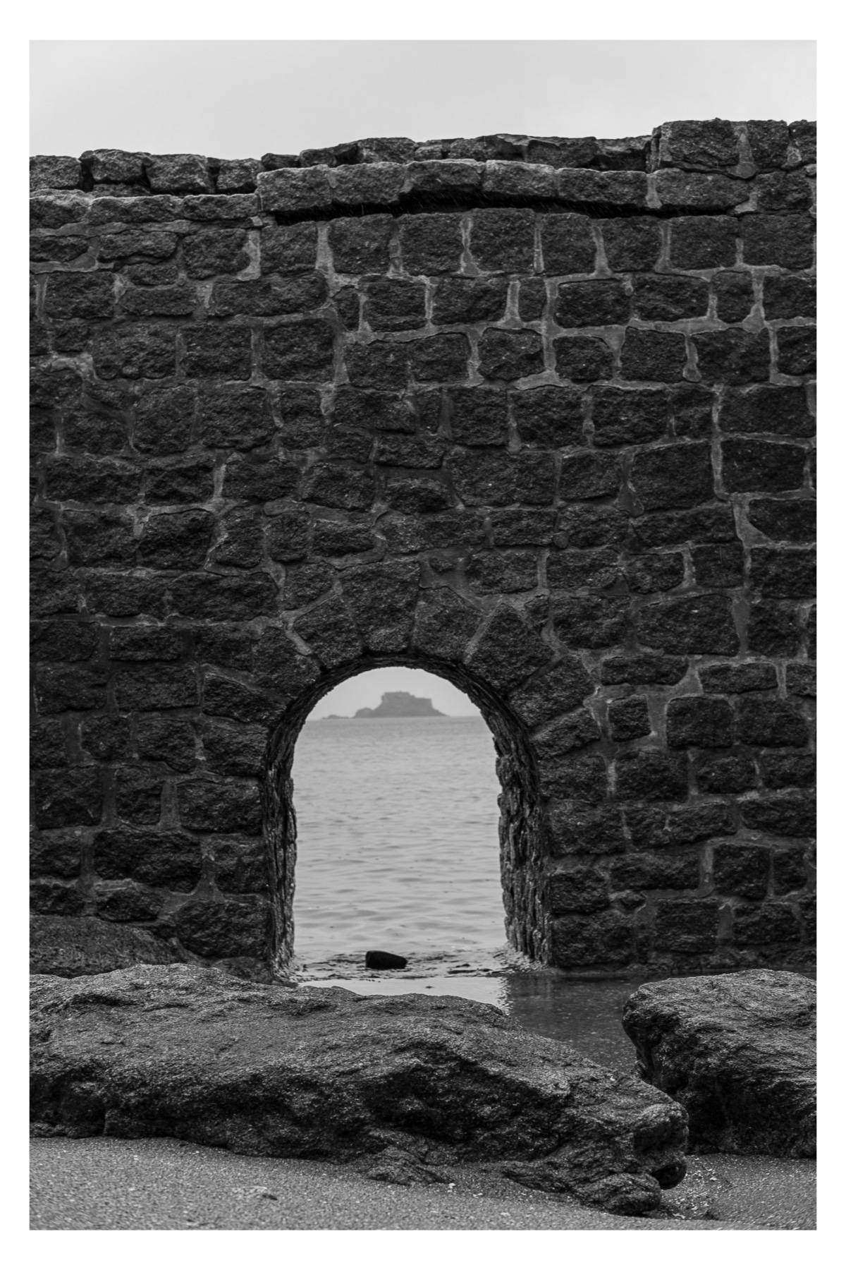 Monochrome photo of Fort de Harbour island framed by the Chemin de Ronde de la Malouine in Dinard France