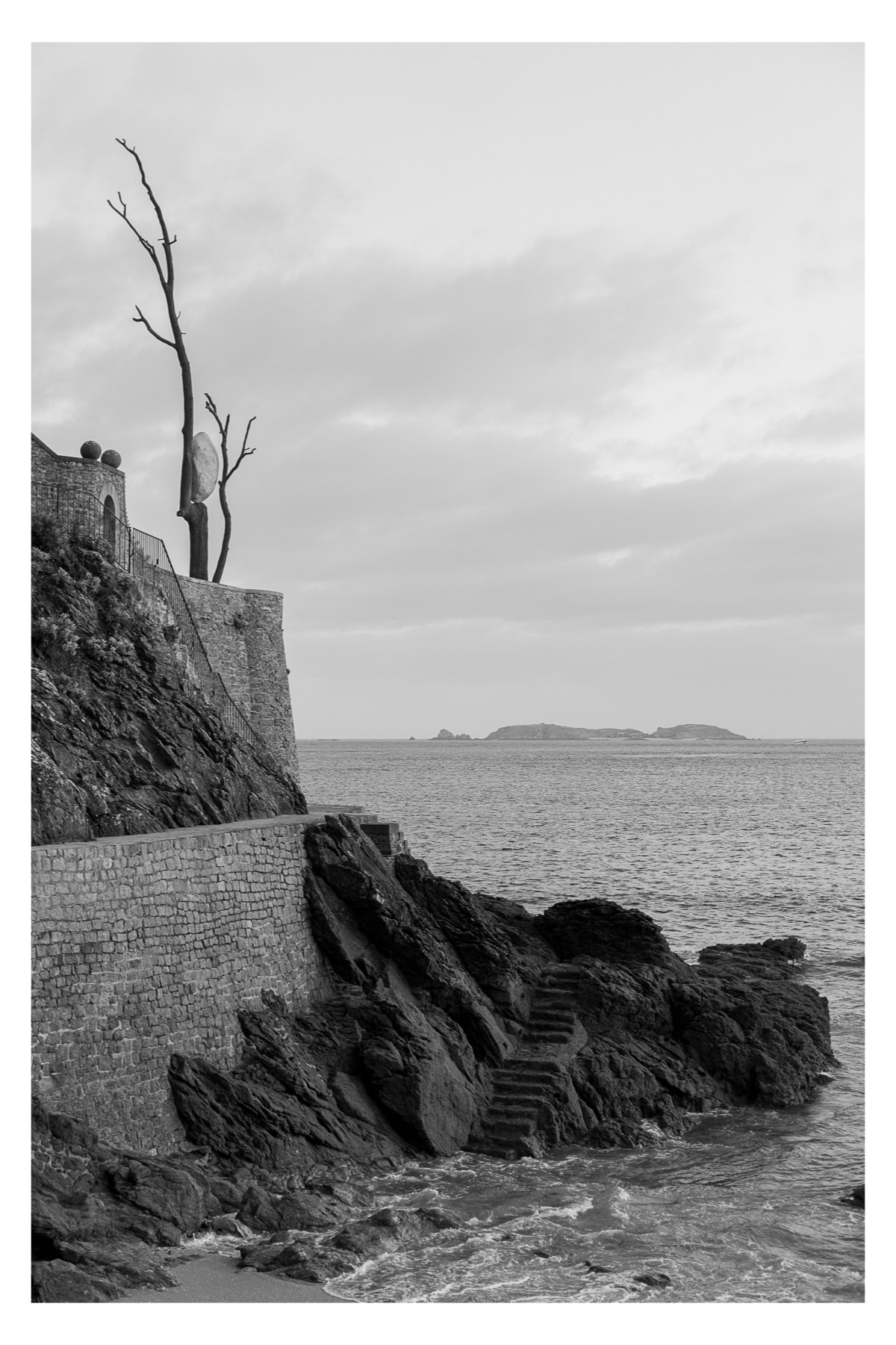 Monochrome photo of a walking path along the ocean with steps leading down into the water below a precariously perched art installation above the walkway.