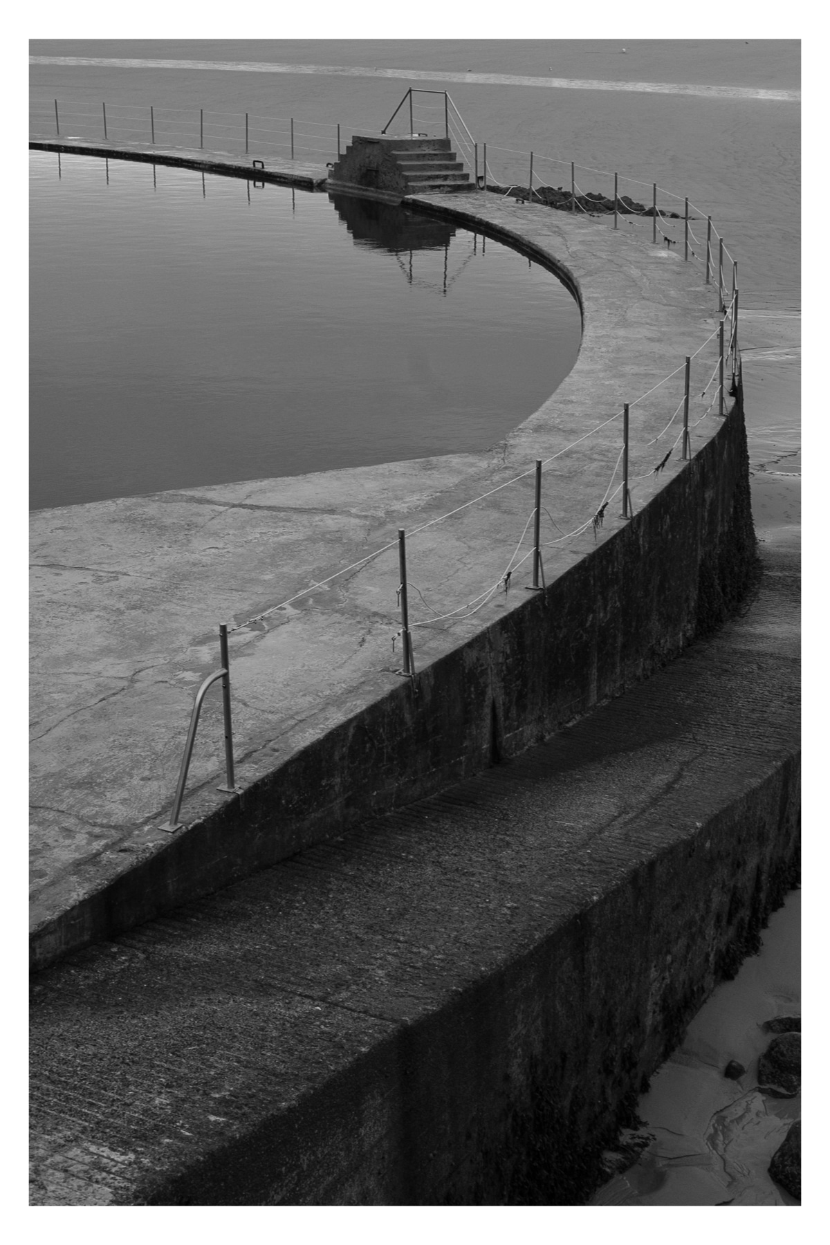 Monochrome photo of an outdoor saltwater pool at the beach in Dinard France.